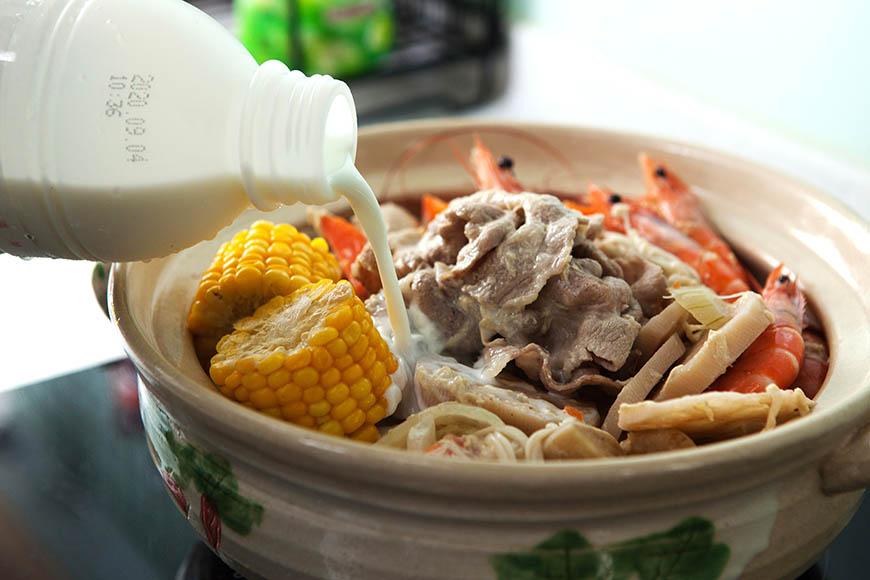 火鍋倒入鮮奶煮滾後,續入火鍋肉片、生豆包、金針菇煮約2 分鐘後即可上桌。