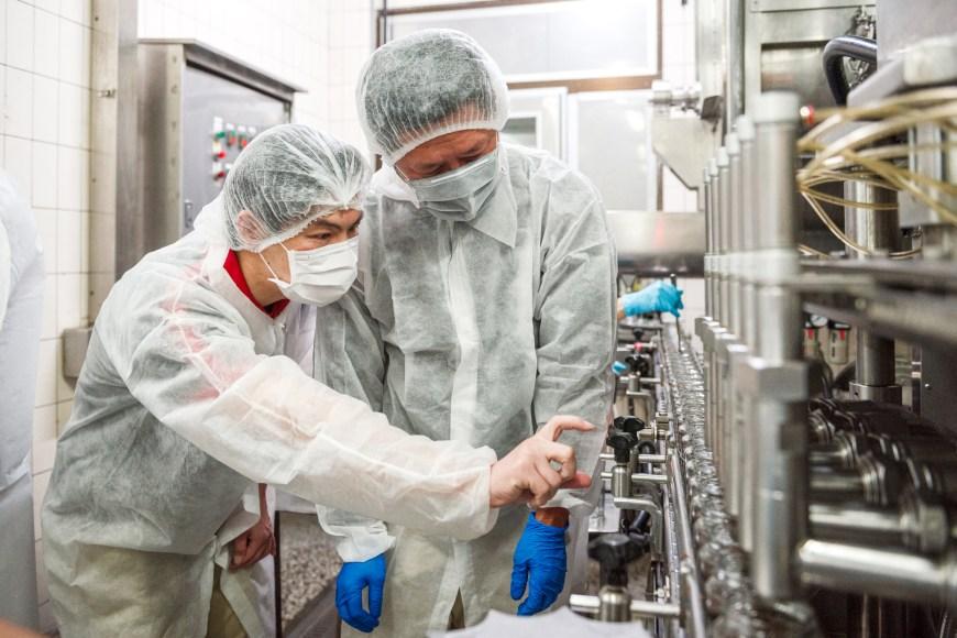 產品專員與生產者檢查油蔥醬產線的油、醬填充後的比例,每一罐都要達到足量的醬料。