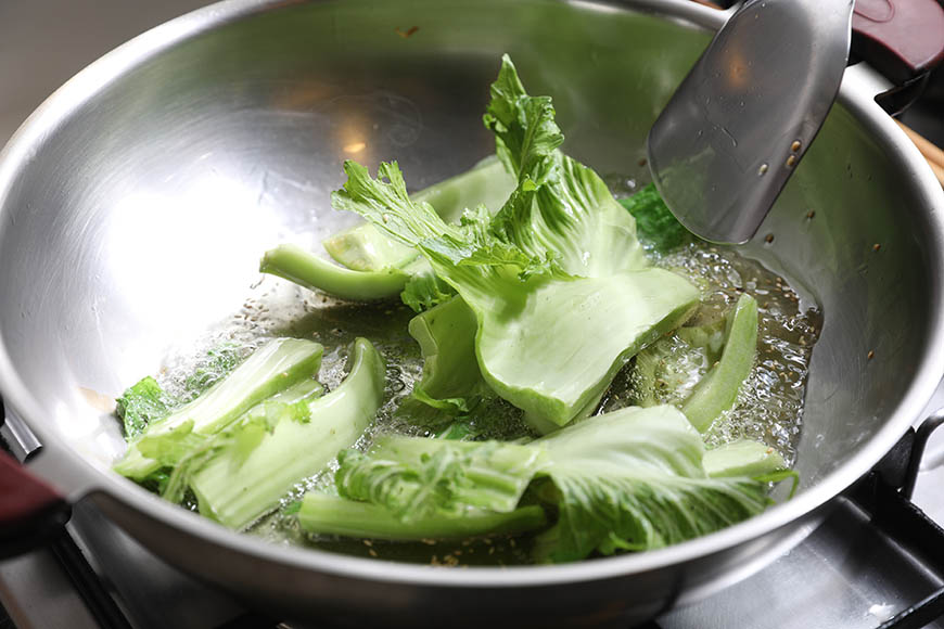 冬季除了白菜,也盛產芥菜,徐婉君自家農場收成時總有一大堆,除了將芥菜葉作成酸菜,芥菜梗便是?芥菜的主要食材。婉君父親來自江蘇,?芥菜是年節時家常料理。「?」的烹調手法是先將主要食材油炸或是略為翻炒,再入蔥段、薑塊熗香,接著入醬料和湯汁,小火滾煮至湯汁收至濃稠狀,藉此把醬料裹上食材並入味,色香俱佳。因?菜用油較多,婉君平常少做,她笑著說:「需要用到比較多油的,像是炸的,都在年節時做,一年只要做一次就好。」此次因料理素菜,減去熗蔥、薑的步驟。如果做得多了,可放冰箱,涼涼的也很好吃,當朋友來做客時,拿出來就是一道小菜。?芥菜,熱油鍋,放入作法1,以中火翻炒至軟。