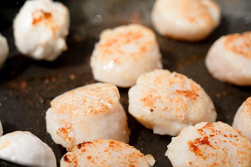 小松菜洗淨、切小段,加1 顆蛋白用果汁機打成泥狀。 鍋入油2 大匙燒熱,炒熟蔬菜泥,並加入2大碗水。 加入略切小段的白精靈菇拌炒,加鹽、胡椒粉調味。 地瓜粉加水1 大匙攪勻後倒入,勾芡成羹汁,加一點胡麻油增添香氣,並且讓羹面光亮。 另起一油鍋煎干貝,如非使用不沾鍋,干貝先裹一層薄薄的麵粉,大火煎比較不會黏鍋。 干貝煎至兩面微焦中間半生即可;同鍋可同時煎花枝丸。 煎熟之干貝、花枝丸均勻分散擺入淺盤,周圍淋入羹汁即成美味又好看的年節菜肴。